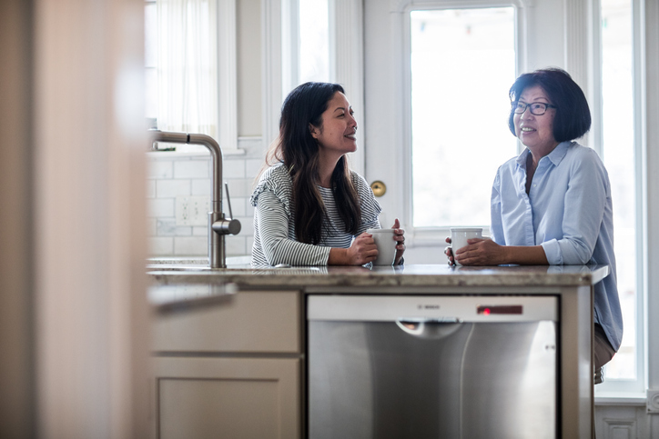 mother and adult daughter having coffee in kitchen